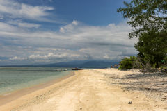Lonely beach in Lombok, Indonesia with boats in the background Royalty Free Stock Images