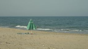 Lonely beach umbrella in sand near sea. Wind blowing on umbrella and towel. Lonely beach umbrella in the sand near the sea. Wind blows on open umbrella and stock video