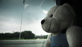 Lonely Bear. A lonely teddy bear staring outside world through a window stock images