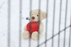 A lonely bear with a big red heart is behind bars. abandoned, sad in search of good hands and soul. help the poor. lonely on royalty free stock photo