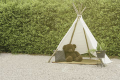 Lonely bear doll in tepee,Indian tent in garden,vintage style. Lonely bear doll in tepee,Indian tent in garden,vintage Royalty Free Stock Photo