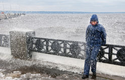 Lonely beatyfull girl in icy splashes of storm waves on the riverside with metal embankment Stock Images