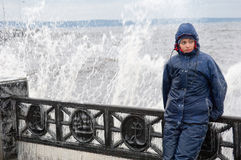 Lonely beatyfull girl in icy splashes of storm waves on the riverside with metal embankment Stock Image