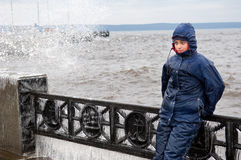 Lonely beatyfull girl in icy splashes of storm waves on the riverside with metal embankment Royalty Free Stock Photos