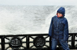 Lonely beatyfull girl in icy splashes of storm waves on the riverside with metal embankment Royalty Free Stock Image