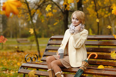 Lonely beautiful girl sitting in autumn park on the wooden bench Royalty Free Stock Photo