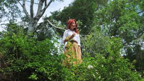 Lonely beautiful red-haired village girl in a forest or park. stock video