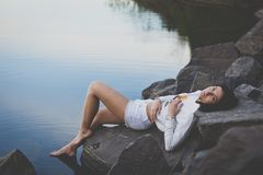 Lonely beautiful sad girl lying on the rocks on the shore of the water, the leg touches the water. open air and open water. Spring stock images