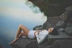 Lonely beautiful sad girl lying on the rocks by the water, cold shadows, the sky goes beyond the horizon, open air and open water stock photo