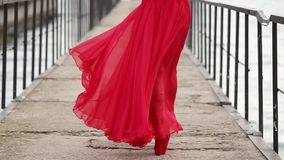 Lonely beautiful woman is going over wharf, back view of her legs and long dress stock video footage