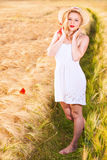 Lonely beautiful young blonde girl in white dress with straw hat Royalty Free Stock Images