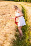 Lonely beautiful young blonde girl in white dress with straw hat Stock Photos