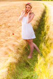Lonely beautiful young blonde girl in white dress with straw hat Stock Images