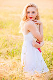 Lonely beautiful young blonde girl in white dress with straw hat Royalty Free Stock Photography