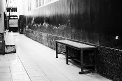 A lonely bech near the wall. A lonely bench laying on the concrete pathway in monochrome toning Royalty Free Stock Photography