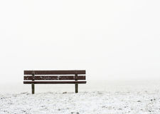 Lonely bench. In a foggy white landscape Stock Images