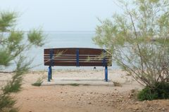 lonely bench on the beach stock photography