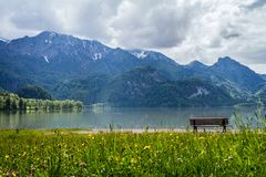 Lonely bench at lake in the mountains with cloudy sky royalty free stock photo