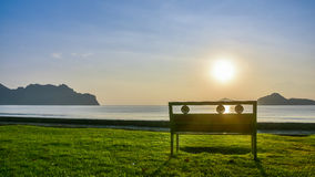 A lonely bench on green grass near the seashore at Ao Manao. In Prachuap Khiri Khan province in southern of Thailand with beautiful blue sky, white cloud Royalty Free Stock Images