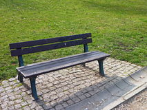 Lonely bench in a green park Stock Photos