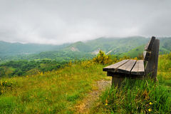 Lonely bench on a hill with mountain scenery Stock Photos