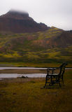 Lonely bench - Iceland. A lonely bench facing the sea under the mountain of Borgafjordur, Iceland Stock Photo