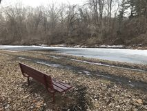 Lonely bench by the icy river stock photo