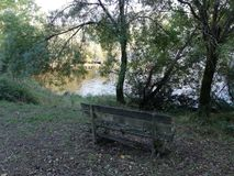 Bench. Lonely bench looking at the Grove and river and autumn leaves surround at it stock photography