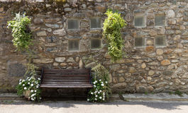 Lonely bench. Near the old castle and old stone wall with the beautiful flowers decoration in village Yvoire, shore the Leman lake, province Auvergne-Rhone Stock Image