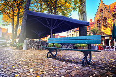 Lonely bench and outdoor cafe in autumn city royalty free stock photography