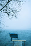 Lonely bench overlooking a winter lake or sea Royalty Free Stock Photo