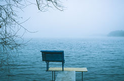 Lonely bench overlooking a winter lake or sea Royalty Free Stock Image