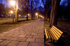 Lonely bench in park. An empty park at dusk.  Long paved lamp-lit path carries eyes into the composition. Horizontal orientation Royalty Free Stock Image