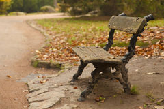 Lonely bench in a park. Lonely bench by a road in autumn park Royalty Free Stock Image