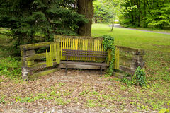 Lonely Bench in Park with Small Wooden Fence Royalty Free Stock Photo