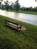 Lonely bench on a river bank stock photos