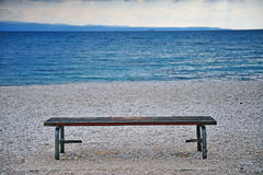Lonely bench at the sea coast Stock Photo