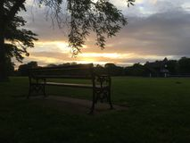 Lonely bench in the sunset. Photo taken in a park Royalty Free Stock Photography