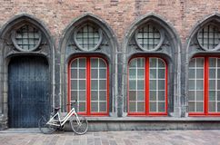 Lonely bicycle standing against the wall of old historical build. Ing in Bruges, Belgium royalty free stock photography