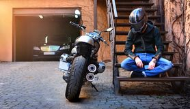 Lonely Biker Thought About And Rested On The Stairs Near The Motorcycle. Motorbike And Motorcyclist In A Helmet. Royalty Free Stock Images