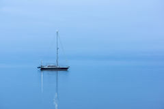 Lonely Black boat in the ocean before sunrise. Lonely Black sailing boat in the ocean before sunrise, during the blue hour, reflections in the water Royalty Free Stock Image