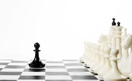 Lonely black pawn in front of enemy team. Courage and boldness. Concept with chess pieces against white background Royalty Free Stock Photo