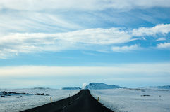 Lonely black road, snow, blue sky, Iceland. Scenery of the lonely road in north of Iceland. The black asphaltic road with yellow street colonnade pillars Royalty Free Stock Images