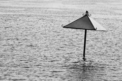 Lonely black and white parasol flooding. Lonely beach umbrella , water flooding in black and white royalty free stock photos