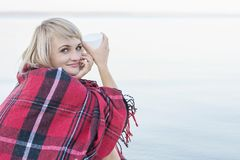 Lonely blond woman on the beach with cup of hot drink, warm red plaid. Pretty alone concept Stock Photo
