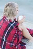 Lonely blond woman on the beach with cup of hot drink, warm red plaid. Pretty alone concept Stock Images