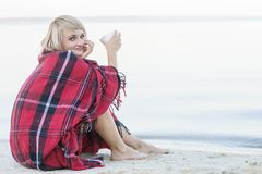 Lonely blond woman on the beach with cup of hot drink, warm red plaid. Pretty alone concept Stock Photography