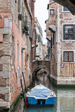 Lonely blue boat on a Venetian canal crossing. Stock Photos