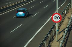 Lonely blue car on highway and SPEED LIMIT signpost in Madrid. Lonely blue car passing through multi lane highway and SPEED LIMIT signpost, on sunset in Madrid royalty free stock photography