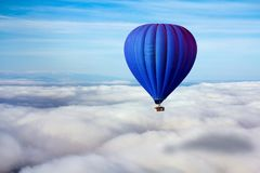 A lonely blue hot air balloon floats above the clouds Stock Images